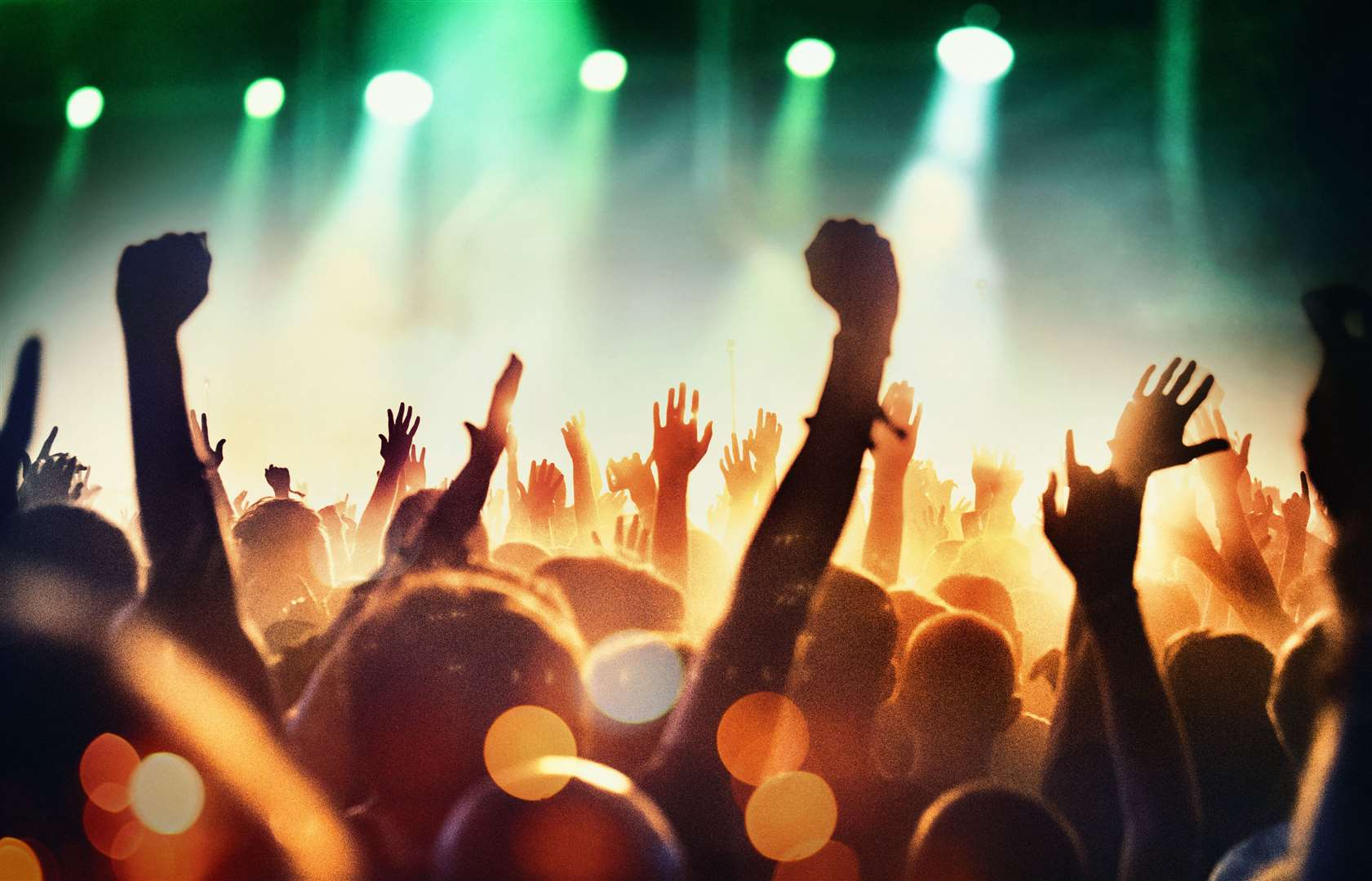 Rear view of large group of unrecognizable people enjoying a concert. Applauding, cheering, shooting video clips. Band is performing on the stage, stage is toned purple and blue while the crowd is lit orange.. (51145168)