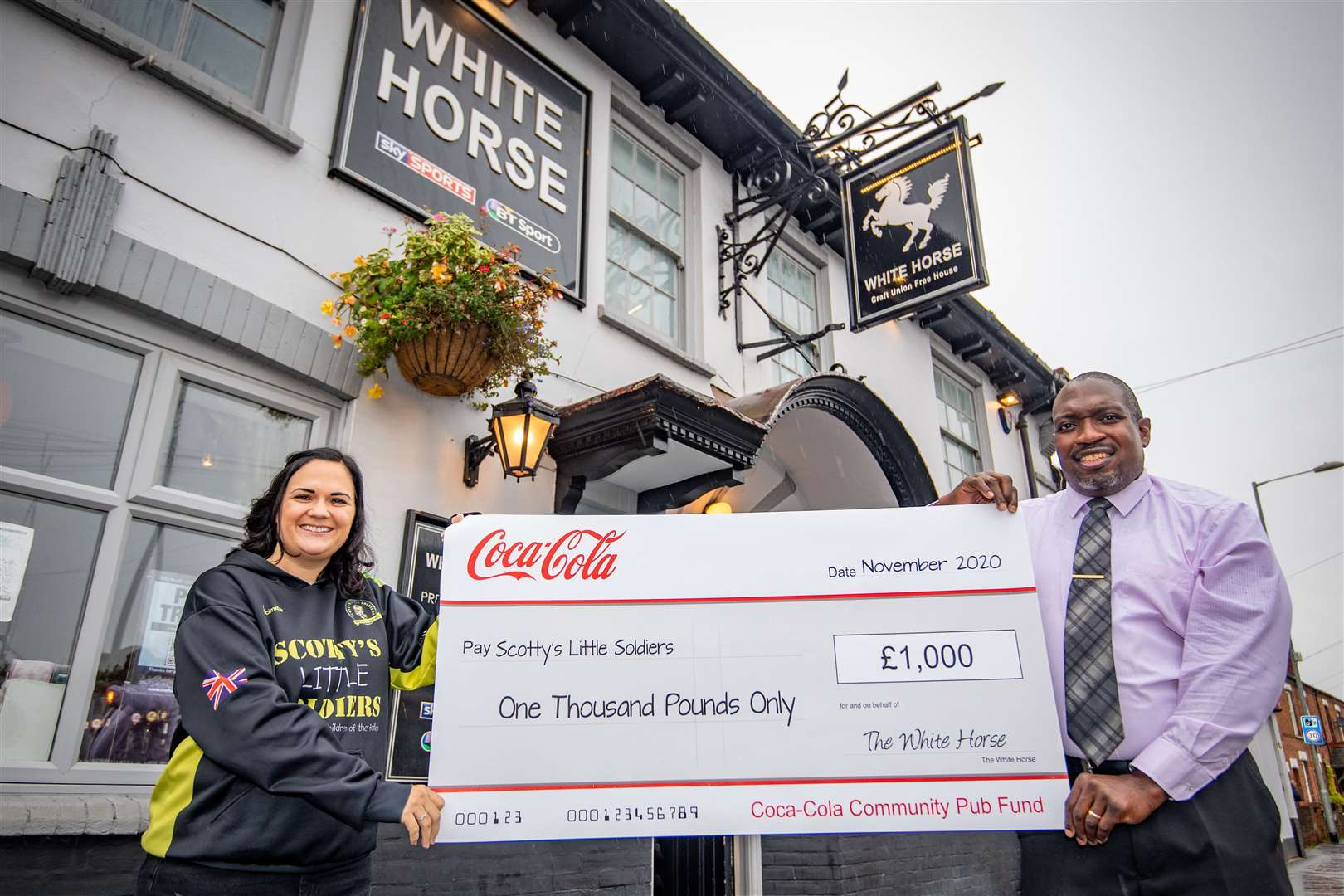 Publican of The White Horse pub Marvin Tillman, 51, and founder of Scotty's Little soldiers Nikki Scott, 39, with the £1k cheque donated to the charity. Picture: SUBMITTED