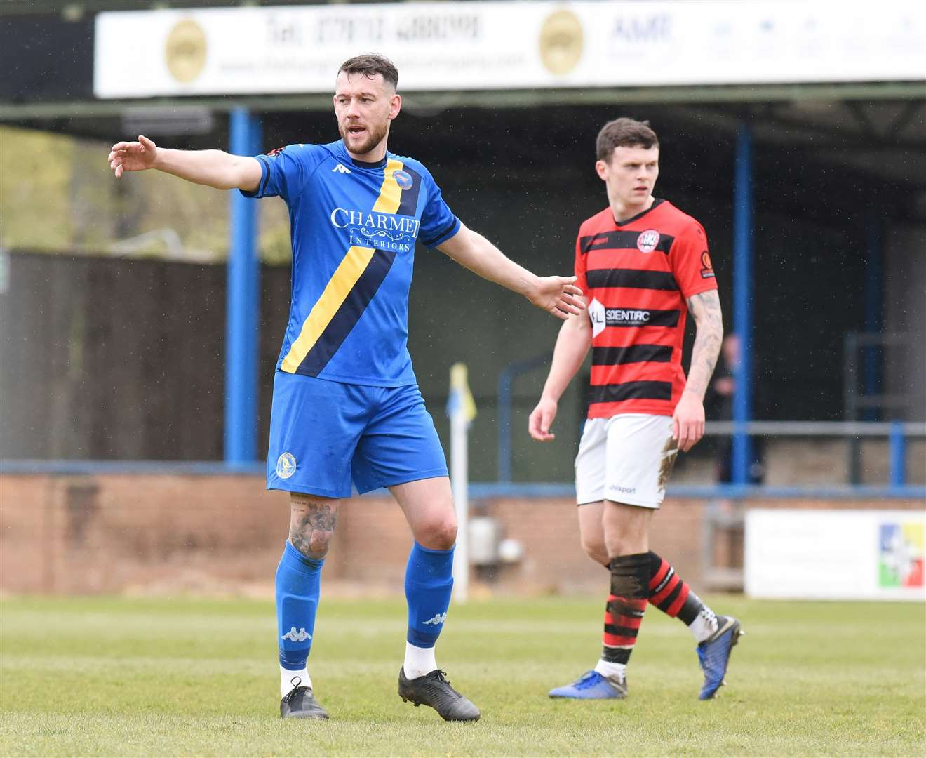 Rory McAuley, seen here in action for King's Lynn Town last month, left, has been suspended by the club.