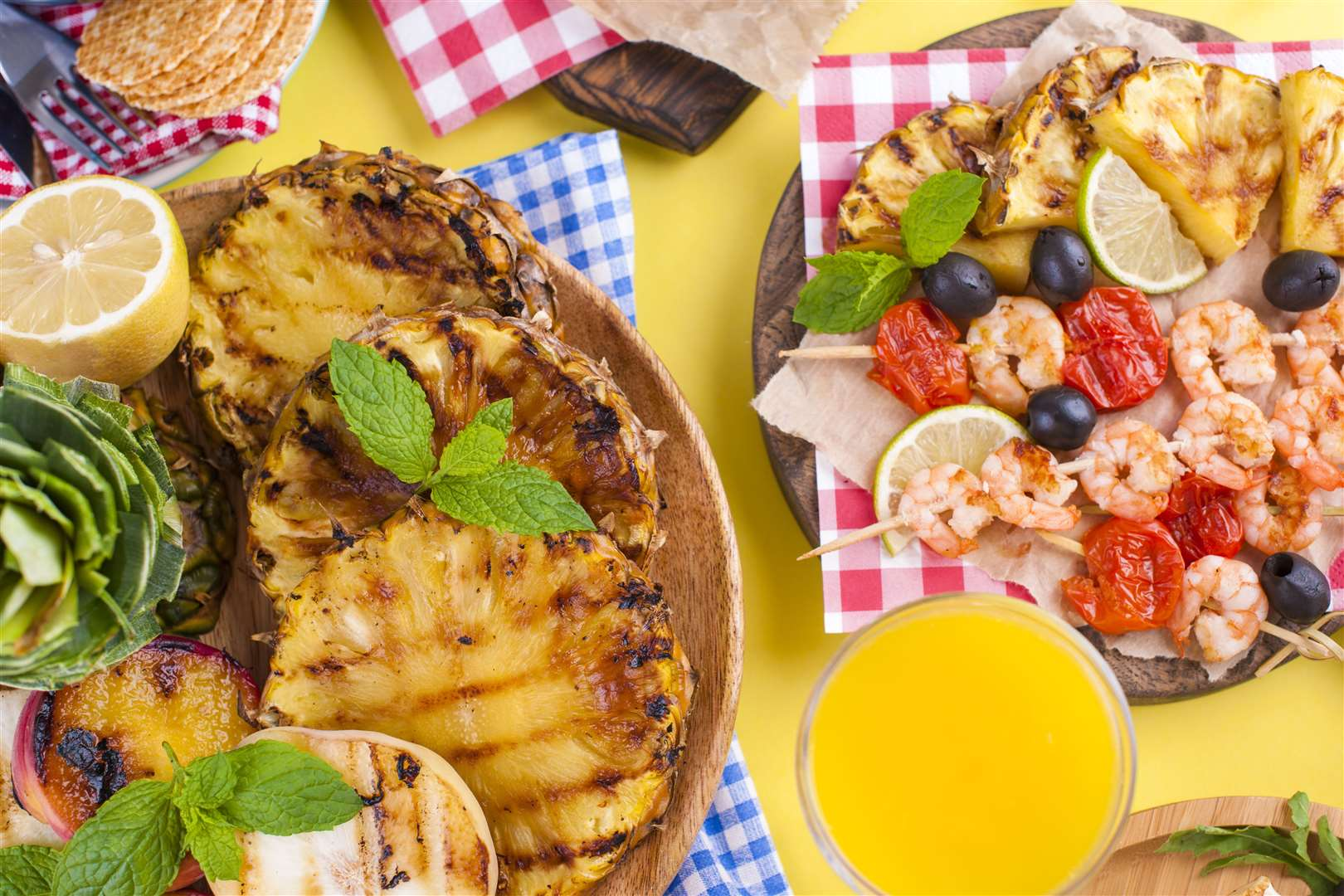 Picnic with grilled food. Sausages and corn on barbecue, shrimp, vegetables and fruits. Delicious summer lunch and plastic dishes. Top view (48521217)