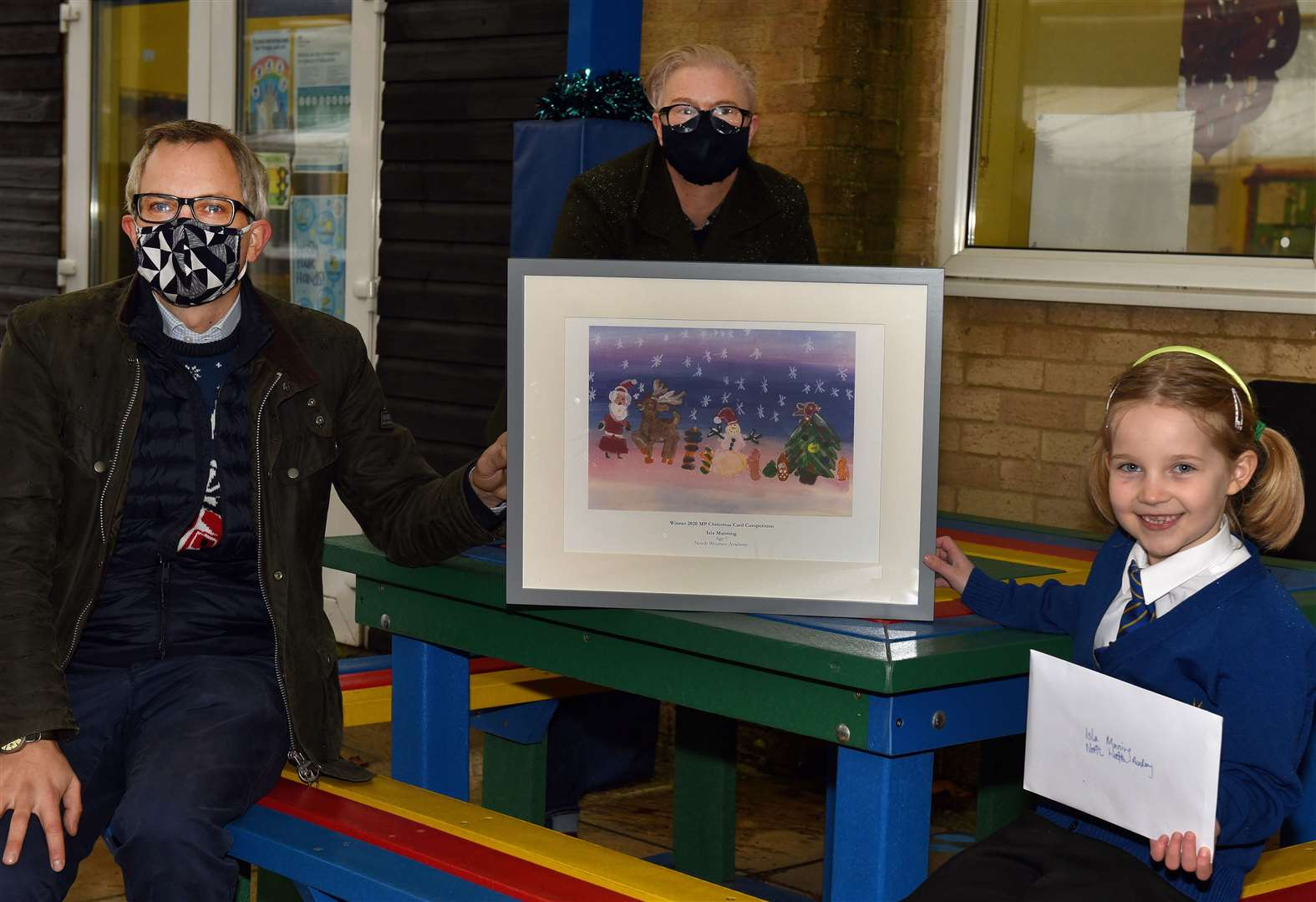 The presentation to Christmas card competition winner at North Wootton Academy. James Wild MP presents a framed print of the winning entry to the artist Isla Manning (7), also in picture is Jenny Richards (Prontaprint King's Lynn owner)