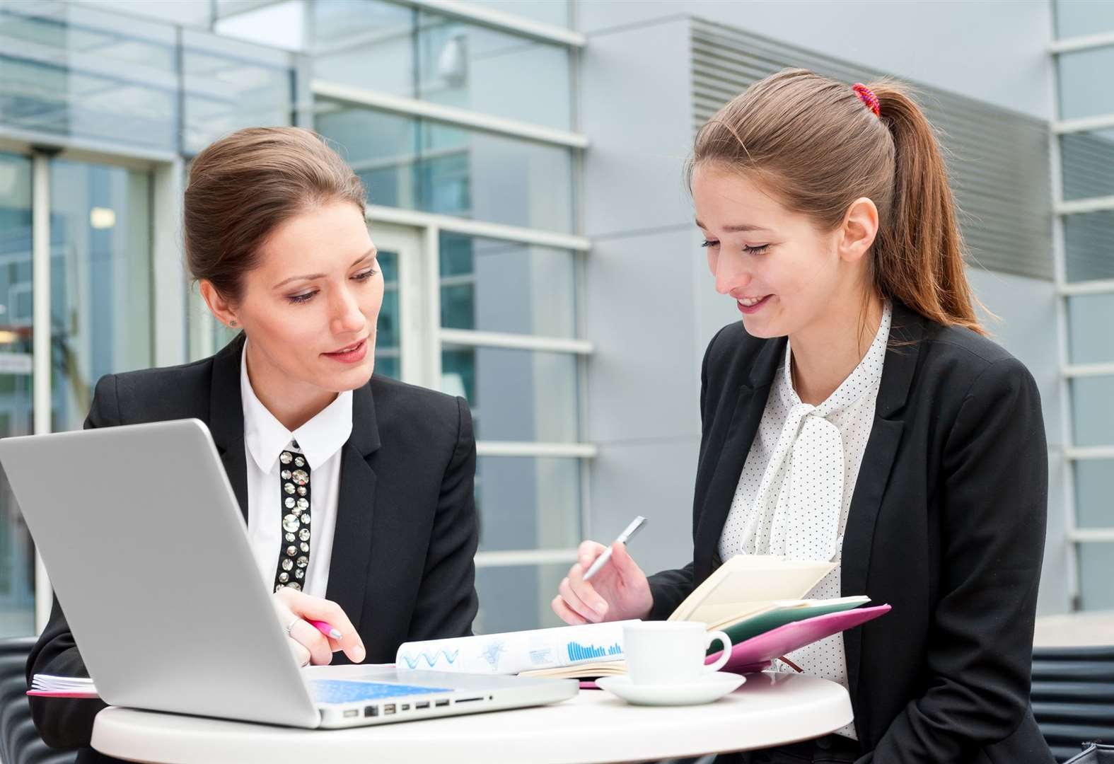Two young business women works together (7643760)